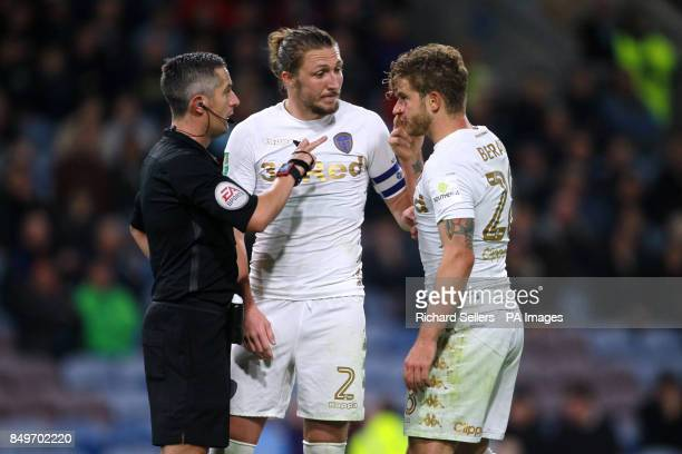 Leeds United's Gaetano Berardi speaks with referee Darren Bond with a cut on his eye during the Carabao Cup third round match at Turf Moor Burnley