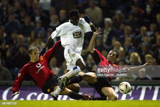 Leeds United's Lamine Sakho is tackled by Manchester United's Phil Neville and Gary Neville