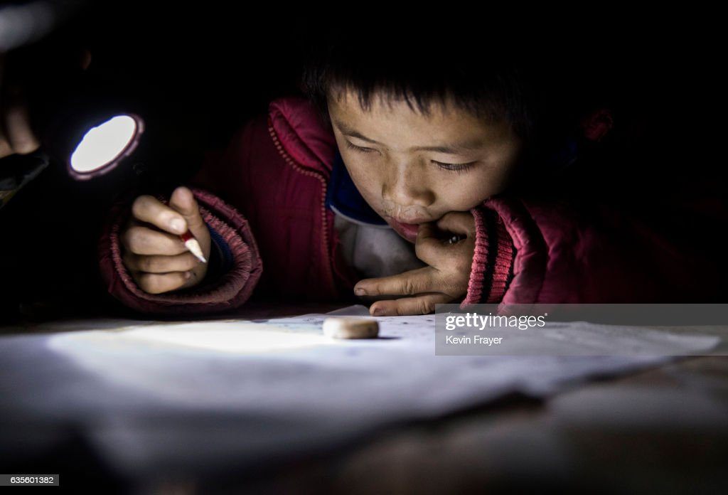 Luo Hongniu, 8, does homework by flashlight at the family's home. Photo by Kevin Frayer/Getty Images