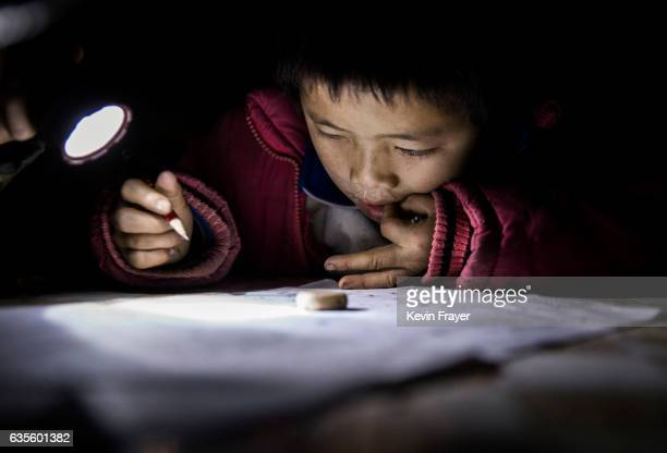 'Left behind' child Luo Hongniu does homework by flashlight at the family's home on December 15 2016 in Anshun China Like millions of Chinese...