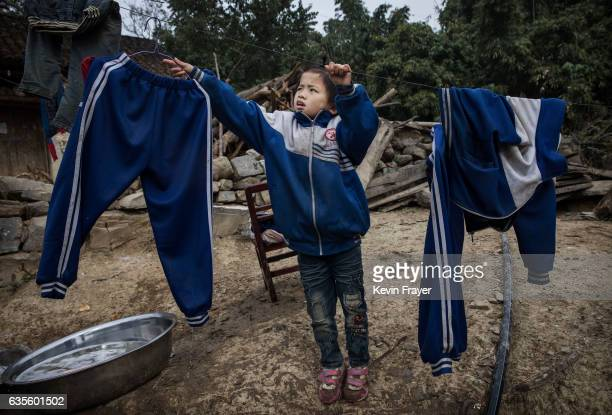'Left behind' child Luo Hongniu hangs laundry after washing clothes with her siblings on December 18 2016 in Anshun China Like millions of Chinese...