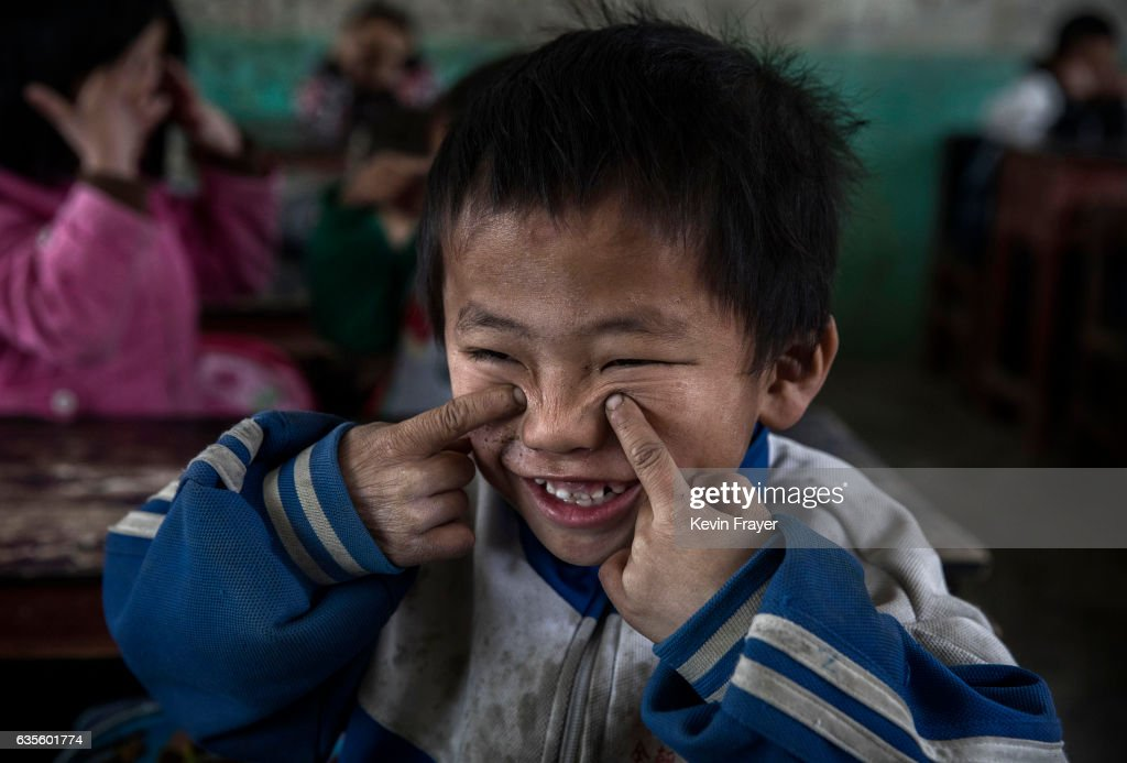 Luo Lie,5, does eye exercises with classmates at a local school. While there are no official figures, a recent government report puts the number of 'left behind' children at nearly 10 million, though child welfare experts estimate the number to be closer to 60 million. Photo by Kevin Frayer/Getty Images