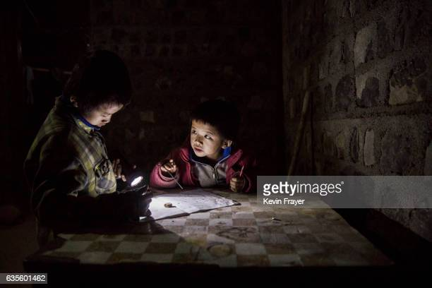 'Left behind' children Luo Gan left and Luo Hongniu do homework together by flashlight at their house on December 15 2016 in Anshun China Like...