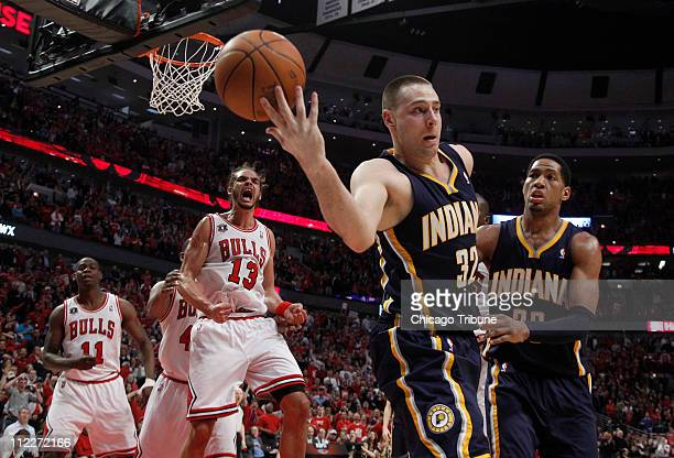 Left Chicago Bulls center Joakim Noah begins the celebration as Indiana Pacers power forward Josh McRoberts loses control of the ball during the...