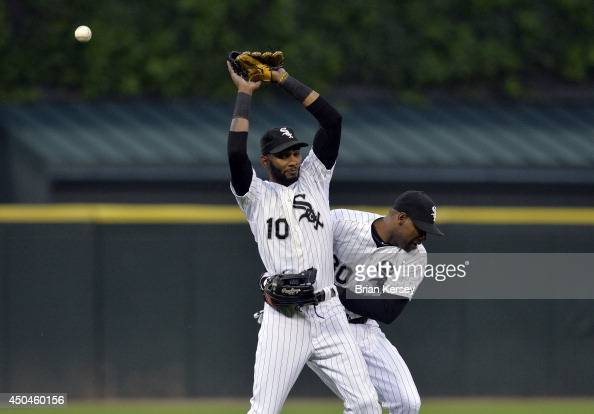 Left fielder Alejandro De Aza of the Chicago White Sox runs into shortstop Alexei Ramirez as he tries to catch a popup hit by Rajai Davis of the...