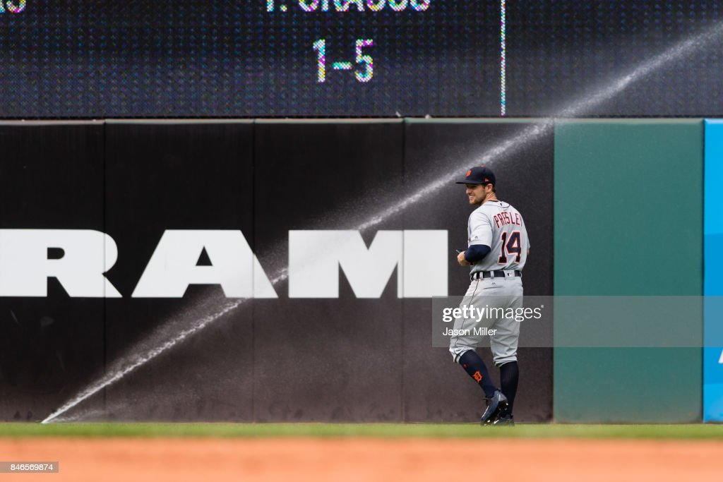 Left fielder Alex Presley #14 of the Detroit Tigers react to a sprinkler in the fifth inning against the Cleveland Indians at Progressive Field on September 13, 2017 in Cleveland, Ohio.
