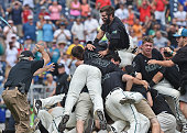 Left fielder Anthony Marks of the Coastal Carolina Chanticleers jumps on top of the dog pile after beating the Arizona Wildcats 43 to win the...
