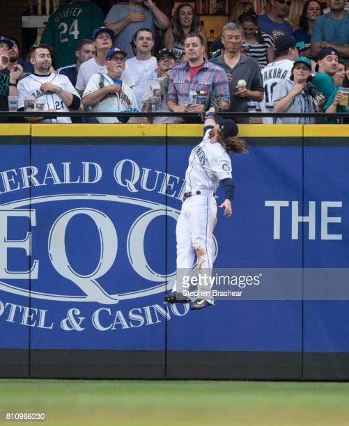 Left fielder Ben Gamel of the Seattle Mariners jump to try and steal a home run by Marcus Semien of the Oakland Athletics off of starting pitcher...