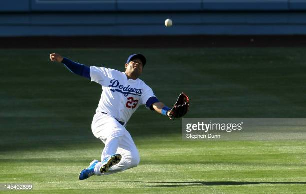 Left fielder Bobby Abreu of the Los Angeles Dodgers makes a sliding catch on a fly ball hit by Ryan Brauyn of the Milwaukee Brewersth end the...