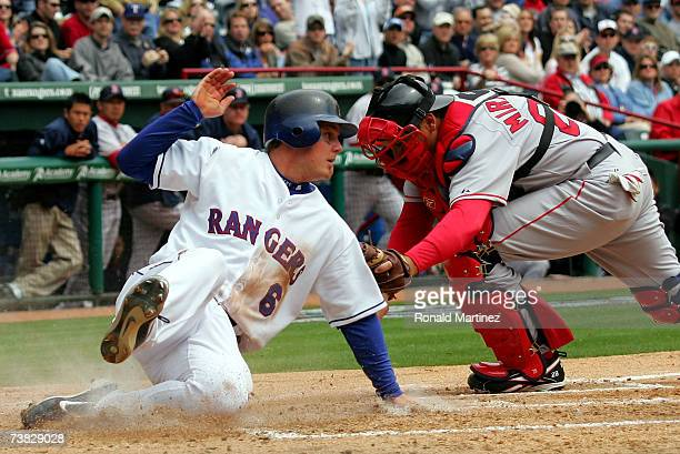 Left fielder Brad Wilkerson of the Texas Rangers scores a run against Doug Mirabelli of the Boston Red Sox during the opening day game on April 6...