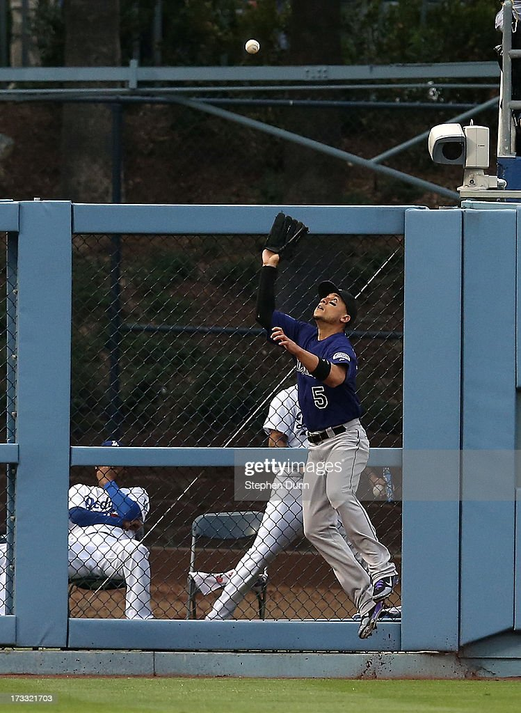 Left fielder Carlos Gonzalez #5 of the Colorado Rockies makes a leaping catch at the wall on a ball hit by Hanley Ramirez of the Los Angeles Dodgers to end the first inning at Dodger Stadium on July 11, 2013 in Los Angeles, California.