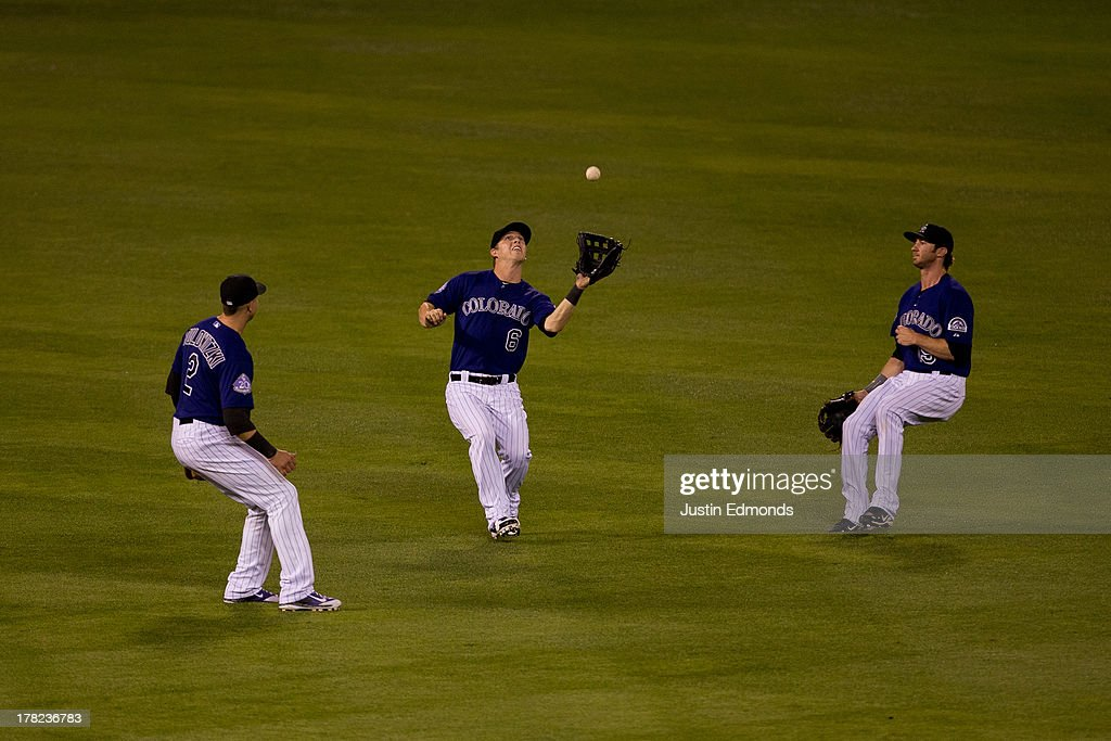 Left fielder Corey Dickerson #6 of the Colorado Rockies makes a catch for the second out of the seventh inning as shortstop <a gi-track='captionPersonalityLinkClicked' href=/galleries/search?phrase=Troy+Tulowitzki&family=editorial&specificpeople=757353 ng-click='$event.stopPropagation()'>Troy Tulowitzki</a> #2 and center fielder Charlie Blackmon #19 look on during a game against the San Francisco Giants at Coors Field on August 27, 2013 in Denver, Colorado. The Giants defeated the Rockies 5-3.