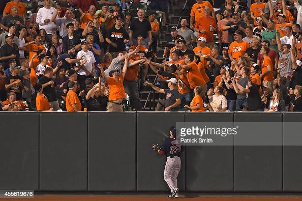 Left fielder Daniel Nava of the Boston Red Sox watches as a ball hit by Adam Jones of the Baltimore Orioles goes into the stands for a two run home...