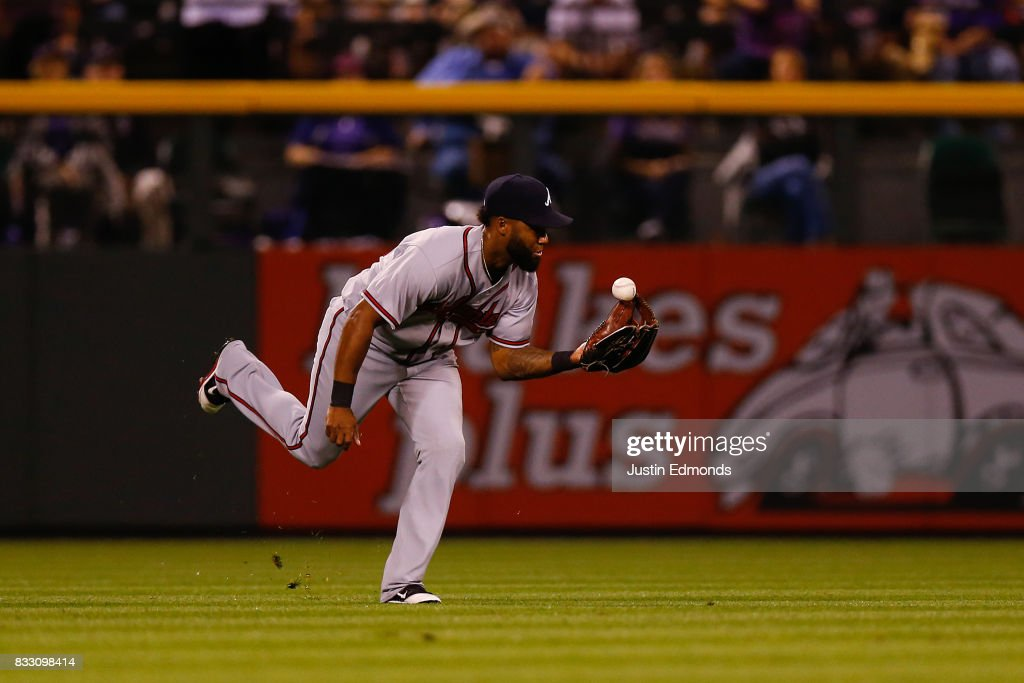Left fielder Danny Santana #23 of the Atlanta Braves makes a juggling catch for an out in the fourth inning against the Atlanta Braves at Coors Field on August 16, 2017 in Denver, Colorado.