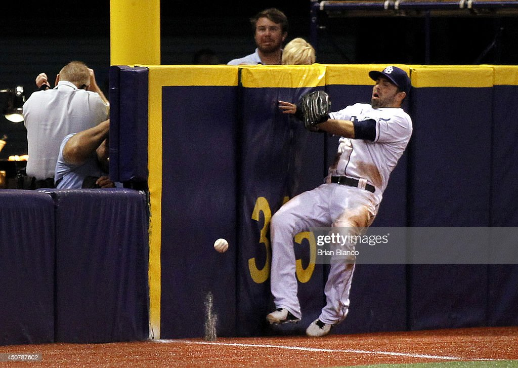 Left fielder <a gi-track='captionPersonalityLinkClicked' href=/galleries/search?phrase=David+DeJesus&family=editorial&specificpeople=206765 ng-click='$event.stopPropagation()'>David DeJesus</a> #7 of the Tampa Bay Rays hits the outfield wall attempting to catch a ball that went for a grand-slam home run by Chris Davis (not pictured) of the Baltimore Orioles during the third inning of a game on June 17, 2014 at Tropicana Field in St. Petersburg, Florida.