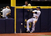 Left fielder David DeJesus of the Tampa Bay Rays hits the outfield wall attempting to catch a ball that went for a grandslam home run by Chris Davis...