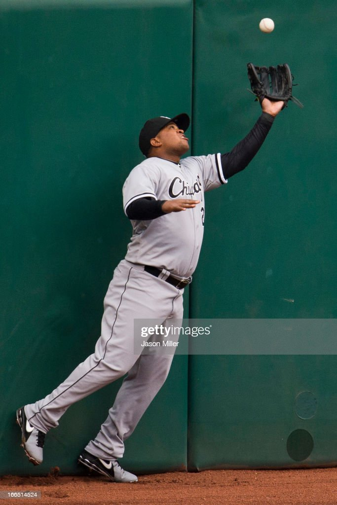Left fielder <a gi-track='captionPersonalityLinkClicked' href=/galleries/search?phrase=Dayan+Viciedo&family=editorial&specificpeople=5720224 ng-click='$event.stopPropagation()'>Dayan Viciedo</a> #24 of the Chicago White Sox bobles a hit by Nick Swisher #33 of the Cleveland Indians during the third inning at Progressive Field on April 13, 2013 in Cleveland, Ohio.