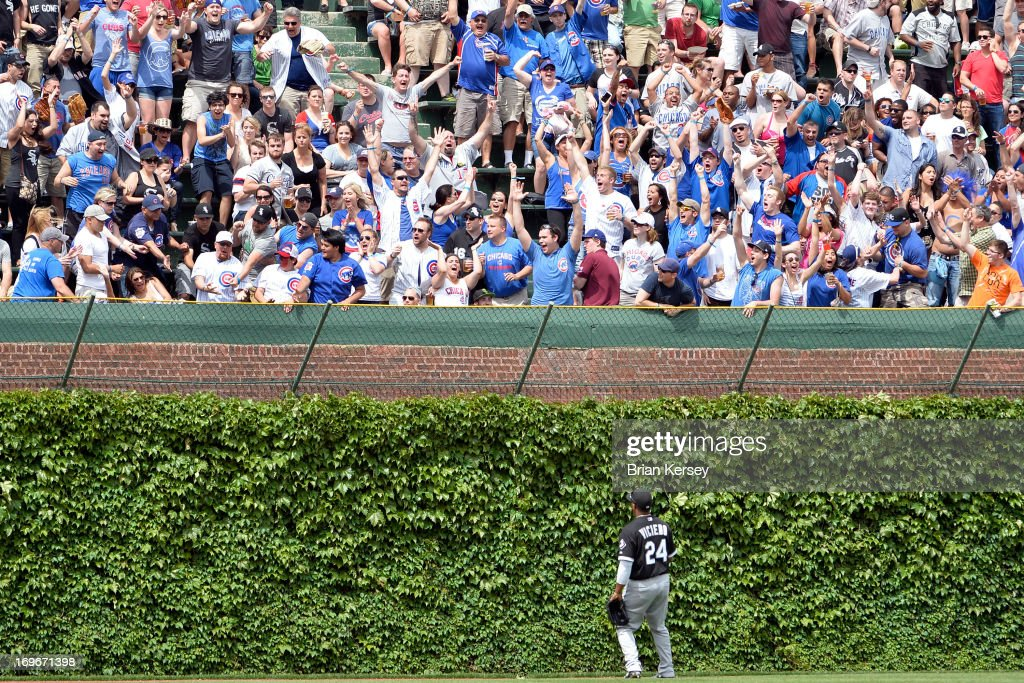 Left fielder Dayan Viciedo #24 of the Chicago White Sox watches as a grand slam hit by Travis Wood #37 of the Chicago Cubs scoring Luis Valbuena #24, Darwin Barney #15 and Welington Castillo #53 leaves the park at Wrigley Field on May 30, 2013 in Chicago, Illinois.