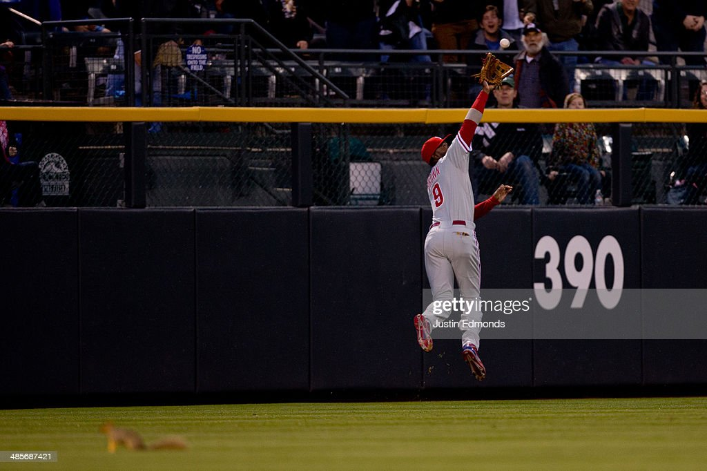 Left fielder <a gi-track='captionPersonalityLinkClicked' href=/galleries/search?phrase=Domonic+Brown&family=editorial&specificpeople=6900643 ng-click='$event.stopPropagation()'>Domonic Brown</a> #9 of the Philadelphia Phillies makes a leaping catch at the warning track on a ball off the bat of Troy Tulowitzki #2 of the Colorado Rockies for the first out of the fourth inning at Coors Field on April 19, 2014 in Denver, Colorado.