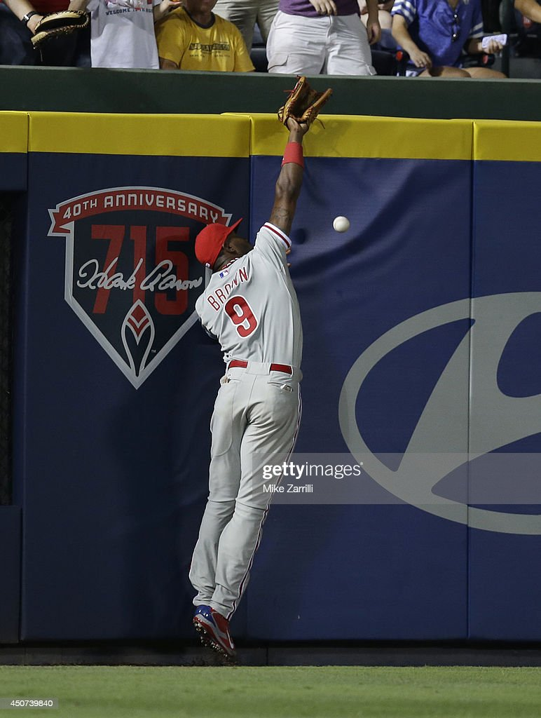 Left fielder <a gi-track='captionPersonalityLinkClicked' href=/galleries/search?phrase=Domonic+Brown&family=editorial&specificpeople=6900643 ng-click='$event.stopPropagation()'>Domonic Brown</a> #9 of the Philadelphia Phillies stretches but can't get to a ball hit by Freddie Freeman #5 of the Atlanta Braves (not pictured) during the game in the 10th inning at Turner Field on June 16, 2014 in Atlanta, Georgia.