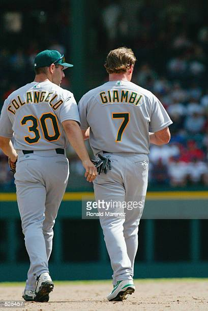 Left fielder Jeremy Giambi of the Oakland Athletics walks on the infield with right fielder Mike Colangelo between innings during the MLB game...