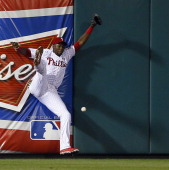 Left fielder John Mayberry Jr #15 of the Philadelphia Phillies can't make a catch against the wall on a ball hit by Josh Rutledge of the Colorado...