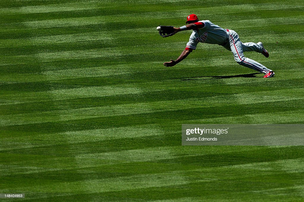 Left fielder <a gi-track='captionPersonalityLinkClicked' href=/galleries/search?phrase=John+Mayberry+Jr.&family=editorial&specificpeople=4959058 ng-click='$event.stopPropagation()'>John Mayberry Jr.</a> #15 of the Philadelphia Phillies makes a diving catch on a line drive by Michael Cuddyer of the Colorado Rockies for the second out of the fourth inning at Coors Field on July 15, 2012 in Denver, Colorado. The Phillies defeated the Rockies 5-1.