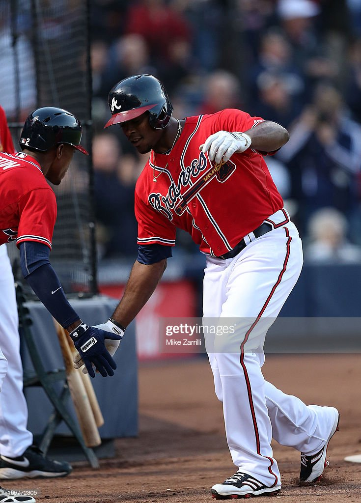 Left fielder <a gi-track='captionPersonalityLinkClicked' href=/galleries/search?phrase=Justin+Upton&family=editorial&specificpeople=846265 ng-click='$event.stopPropagation()'>Justin Upton</a> #8 of the Atlanta Braves is congratulated by his brother and teammate <a gi-track='captionPersonalityLinkClicked' href=/galleries/search?phrase=B.J.+Upton&family=editorial&specificpeople=810704 ng-click='$event.stopPropagation()'>B.J. Upton</a> # 2 after hitting a first inning home run during the game against the Chicago Cubs at Turner Field on April 5, 2013 in Atlanta, Georgia.