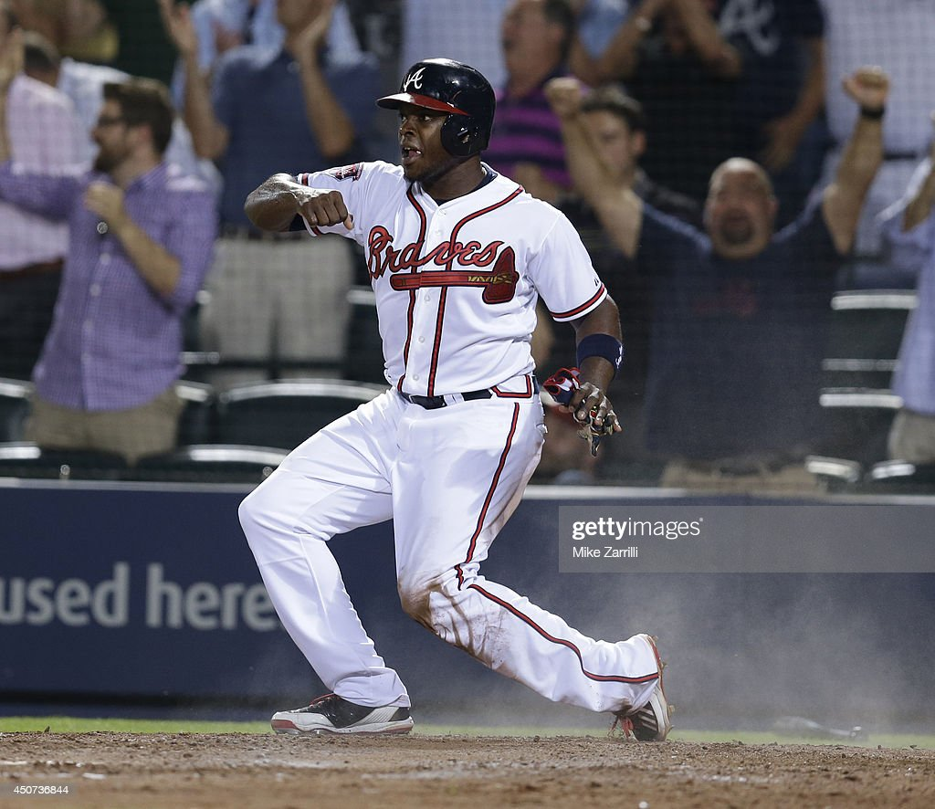 Left fielder <a gi-track='captionPersonalityLinkClicked' href=/galleries/search?phrase=Justin+Upton&family=editorial&specificpeople=846265 ng-click='$event.stopPropagation()'>Justin Upton</a> #8 of the Atlanta Braves slides into home plate in the ninth inning to tie the game against the Philadelphia Phillies at Turner Field on June 16, 2014 in Atlanta, Georgia.