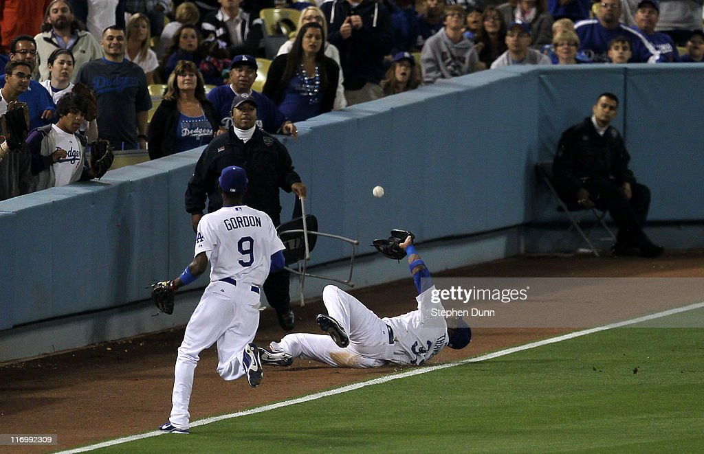Left fielder <a gi-track='captionPersonalityLinkClicked' href=/galleries/search?phrase=Marcus+Thames&family=editorial&specificpeople=215472 ng-click='$event.stopPropagation()'>Marcus Thames</a> #33 of the Los Angeles Dodgers slides but can't hold on to a foul fly ball as shortstop Dee Gordon #9 chases the play against the Houston Astros in the fifth inning on June 18, 2011 at Dodger Stadium in Los Angeles, California.