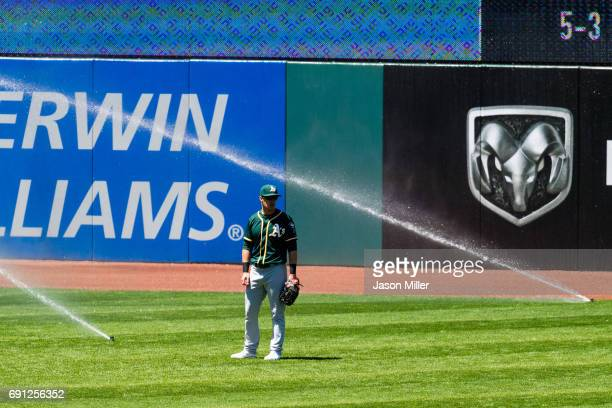 Left fielder Mark Canha of the Oakland Athletics waits for the sprinklers to be turned off during the sixth inning against the Cleveland Indians at...