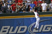 Left fielder Matt Diaz of the Atlanta Braves jumps over the fence and tries unsuccessfully to catch a home run ball hit by Pedro Feliz of the...