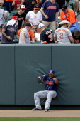 Left fielder Michael Brantley of the Cleveland Indians falls against the wall after missing a three run home run by Robert Andino of the Baltimore...