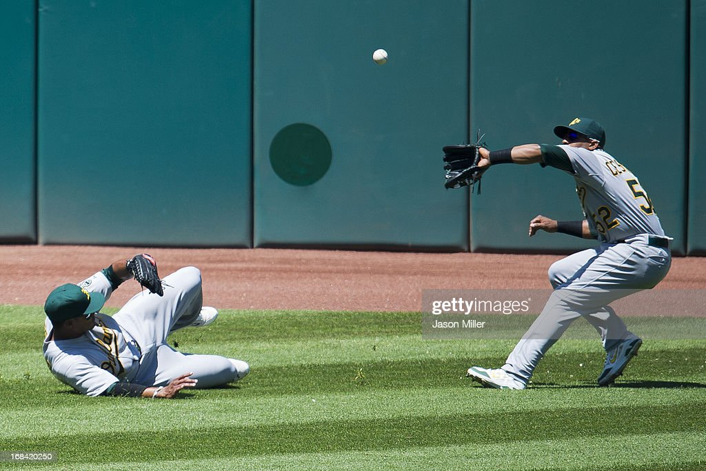 Left fielder Michael Taylor #23 slides as center fielder <a gi-track='captionPersonalityLinkClicked' href=/galleries/search?phrase=Yoenis+Cespedes&family=editorial&specificpeople=8892047 ng-click='$event.stopPropagation()'>Yoenis Cespedes</a> #52 of the Oakland Athletics catches a fly ball hit by Jason Giambi #25 of the Cleveland Indians during the third inning at Progressive Field on May 9, 2013 in Cleveland, Ohio.