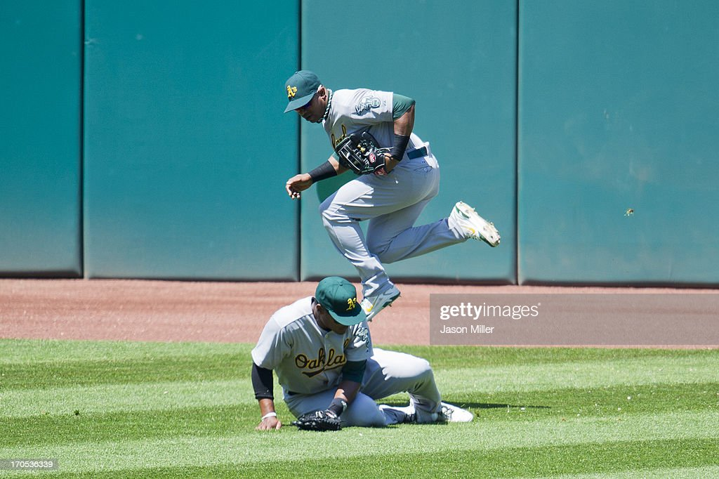 Left fielder Michael Taylor #23 slips and falls as center fielder <a gi-track='captionPersonalityLinkClicked' href=/galleries/search?phrase=Yoenis+Cespedes&family=editorial&specificpeople=8892047 ng-click='$event.stopPropagation()'>Yoenis Cespedes</a> #52 of the Oakland Athletics catches a fly ball hit by Jason Giambi #25 of the Cleveland Indians during the third inning at Progressive Field on May 9, 2013 in Cleveland, Ohio.
