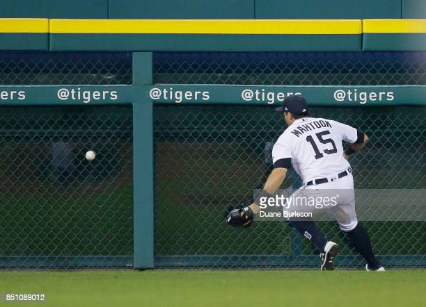 Left fielder Mikie Mahtook of the Detroit Tigers chases down a double hit by Joe Mauer of the Minnesota Twins that drove in two runs during the sixth...