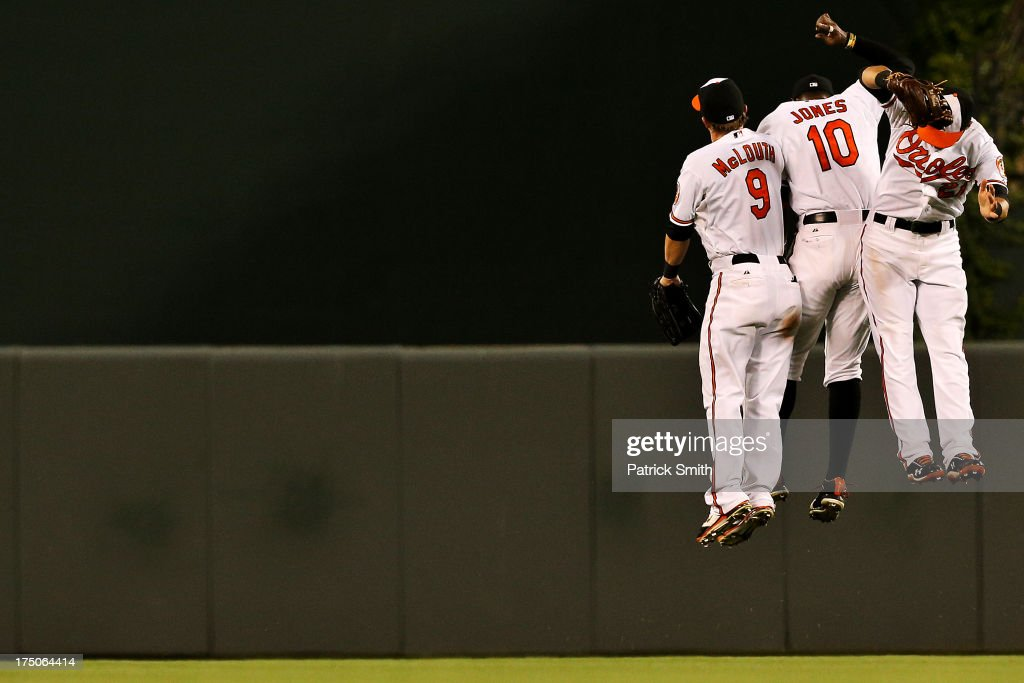 Left fielder Nate McLouth #9, Adam Jones #10 and Nick Markakis #21 of the Baltimore Orioles celebrate after defeating the Houston Astros at Oriole Park at Camden Yards on July 30, 2013 in Baltimore, Maryland. The Baltimore Orioles won, 4-3.