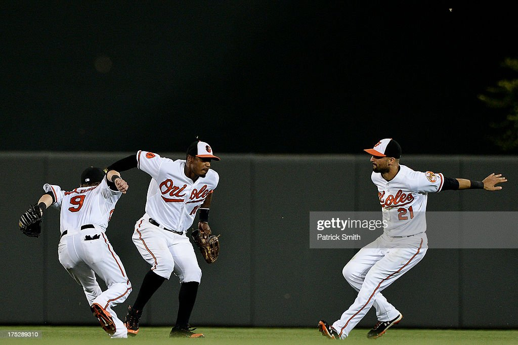 Left fielder Nate McLouth #9, Adam Jones #10 and Nick Markakis #21 of the Baltimore Orioles celebrate after defeating the Houston Astros at Oriole Park at Camden Yards on August 1, 2013 in Baltimore, Maryland. The Baltimore Orioles won, 6-3.