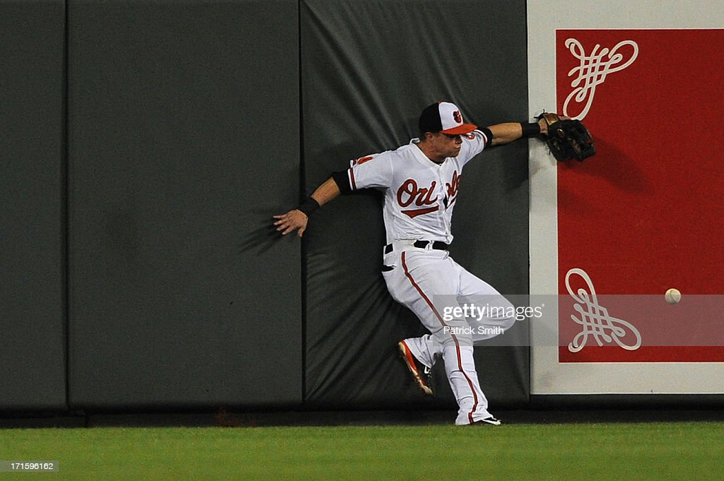 Left fielder <a gi-track='captionPersonalityLinkClicked' href=/galleries/search?phrase=Nate+McLouth&family=editorial&specificpeople=536572 ng-click='$event.stopPropagation()'>Nate McLouth</a> #9 of the Baltimore Orioles crashes into the outfield wall after missing a hit by designated hitter Jason Giambi #25 of the Cleveland Indians (not pictured) in the ninth inning at Oriole Park at Camden Yards on June 26, 2013 in Baltimore, Maryland. The Cleveland Indians won, 4-3.
