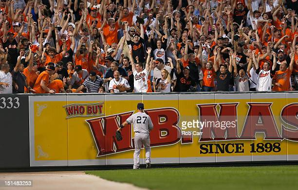 Left fielder Raul Ibanez of the New York Yankees looks on as fans celebrate a three RBI home run hit by Matt Wieters of the Baltimore Orioles during...