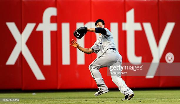 Left fielder Ryan Braun of the Milwaukee Brewers goes back after misjudging a fly ball hit by Freddy Galvis of the Philadelphia Phillies during the...