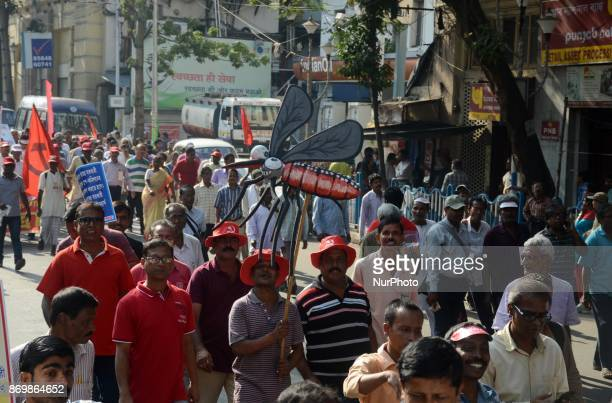Left front activists protesting with a symbol of a mosquito against the government for spreading the dengue during the mass rally in Kolkata India on...