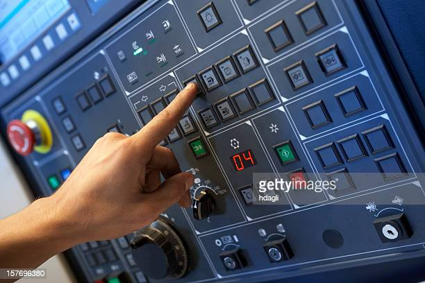 Left hand pressing buttons on a control panel