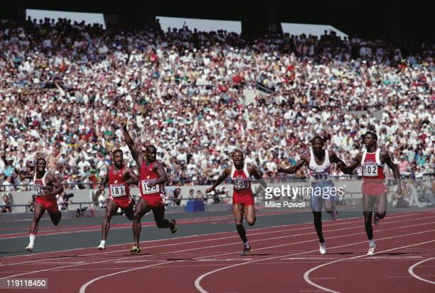 Left right Dennis Mitchell and Desai Williams look across at Ben Johnson of Canada who holds his arm aloft in victory over Calvin Smith of the USA...