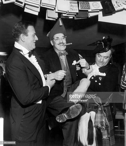 American actor John Wayne with comedians Groucho Marx and Red Skelton at a Christmas party circa 1955