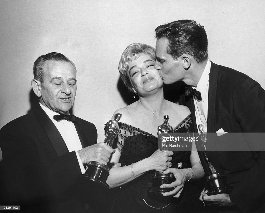 American director William Wyler (1902 - 1981), French actress Simone Signoret (1921 - 1985) and American actor Charlton Heston with their trophies at the Academy Awards ceremony, held at the RKO Pantages Theatre, Los Angeles, California, 4th April 1960. Signoret won Best Actress for her role in 'Room at the Top', while Heston and Wyler won Best Actor and Best Director respectively for 'Ben Hur'.