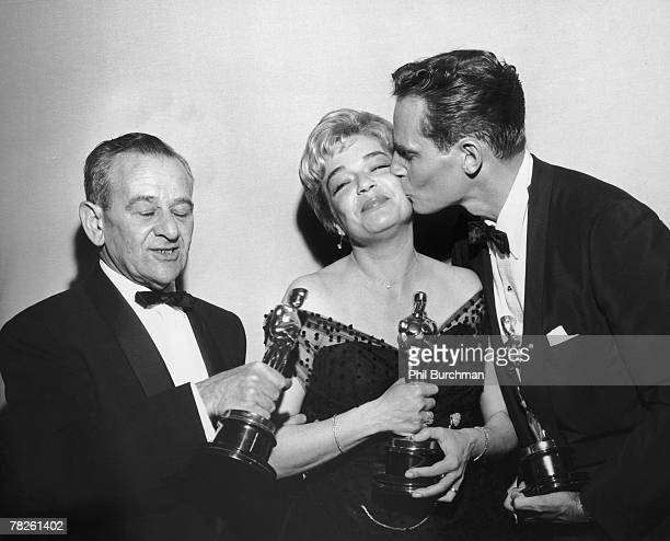 American director William Wyler French actress Simone Signoret and American actor Charlton Heston with their trophies at the Academy Awards ceremony...