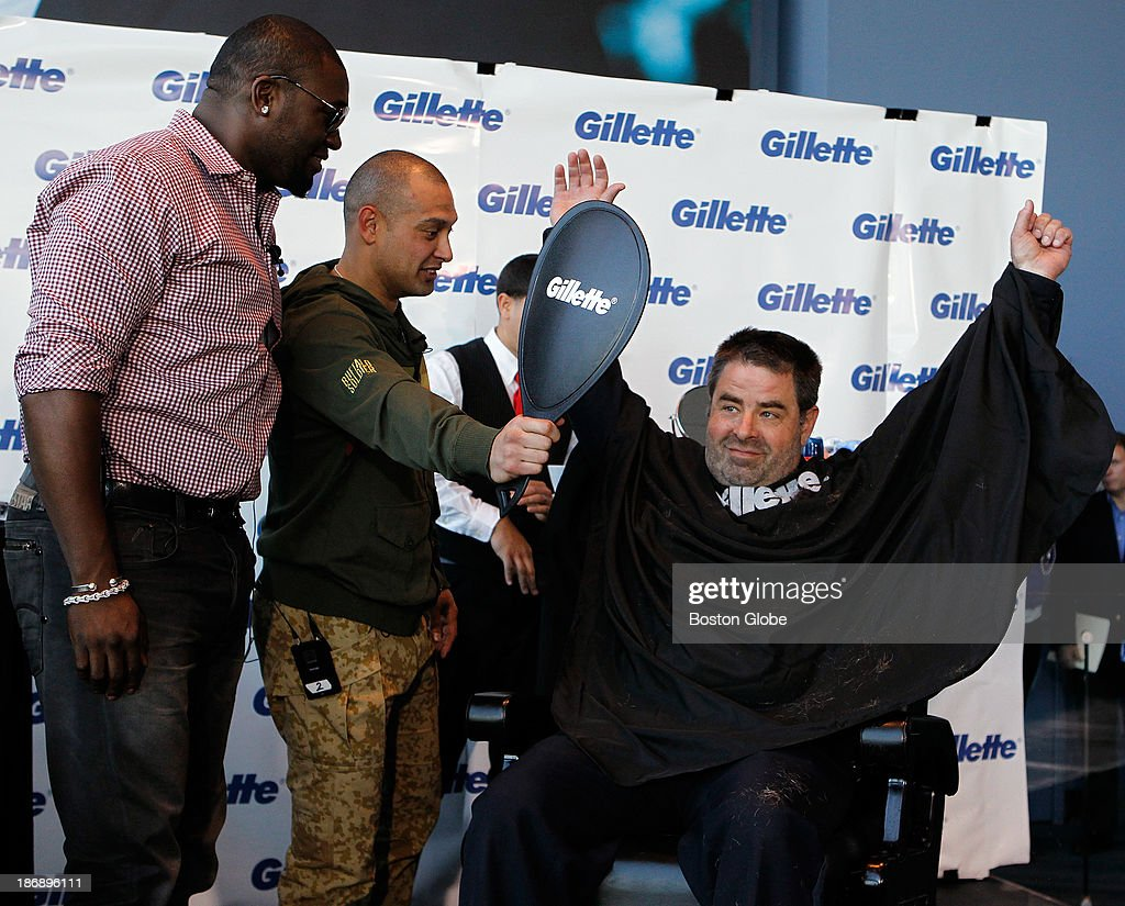 Left to right, Boston Red Sox players David Ortiz and Shane Victorino look on as Bullpen officer Steve Horgan reacts after having his beard shaved off at Gillette World Shaving Headquarters in Boston on November 4, 2013. Gillette donated $100,000 to the One Fund Boston after the shave.