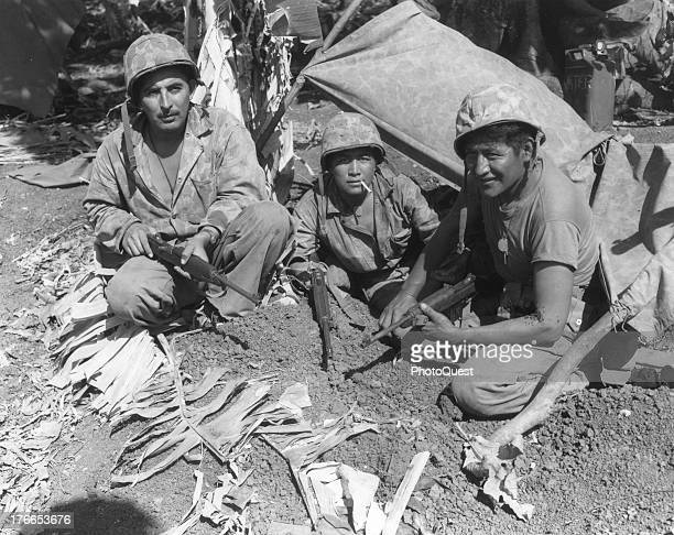 Left to right Corporal Oscar Ithma Private First Class Jack Nez and Private First Class Carl Gorman Navajo Indian communication men with the Marines...