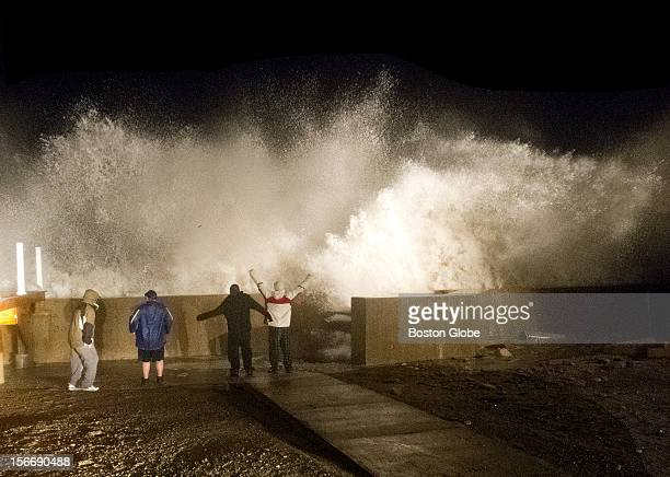 Left to right Dan Cowing Joseph Holmes AJ Roache and Scott Stohlberg standing in front of the sea wall as the evening high tide storm surge hits the...